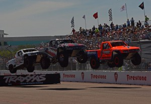 Robby Gordon leads two other trucks over a ramp as Gordon's Soeed Off-Road Traxxas performs in the sescond of two races.  [Joe Jennings Photo]