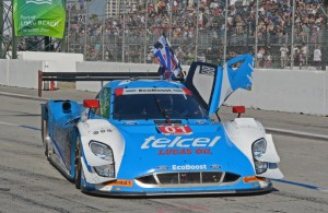 Winning Ganassi Ford EcoBoost drives to victory lane with checkered flag flying and door open.  [Joe Jennings Photo]