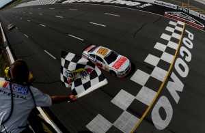 Dale Earnhardt Jr. crosses the finish line to win the Pocono 400 at Pocono Raceway on June 8, 2014.  [Credit: NASCAR Via Getty Images]