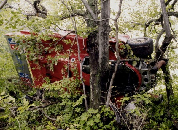 The Jim Mullen piloted Coke Porsche 962 stuck in the trees after flying off the track at Turn 6 in 1985.  [Photo by Jack Webster]