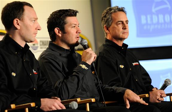 Martin Truex Jr, driver of the #78 Furniture Row Chevrolet, answers questions from the media as Cole Pearn (L), crew chief of the #78 Furniture Row Chevrolet, and Joe Garone (R), general manager of Furniture Row Racing, look on during day 4 of the Charlotte Motor Speedway NASCAR Media Tour.  [Credit: Jared C. Tilton/NASCAR via Getty Images]