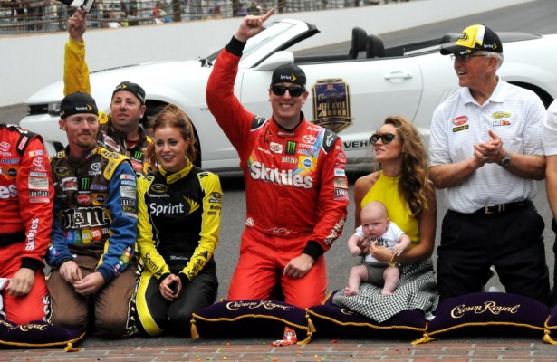 "Kyle Busch along with his family, Joe Gibbs and the JGR team celebrate at the ""Yard of Bricks"". [Father Dale Grubba Photo]"