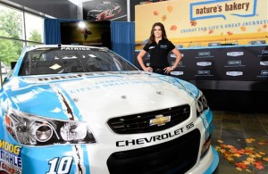 Danica Patrick poses with the new Nature's Bakery #10 Stewart-Haas Racing Chevrolet. [Photo by Jared C. Tilton/Getty Images for Stewart-Haas Racing]