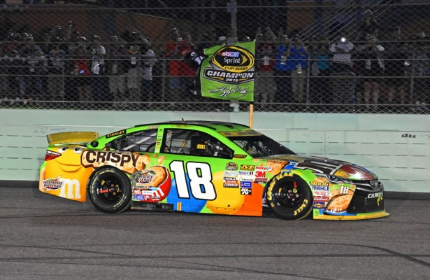 Sprint Cup champion Kyle Busch carries victory flag down frontsretch. [Joe Jennings Photo]