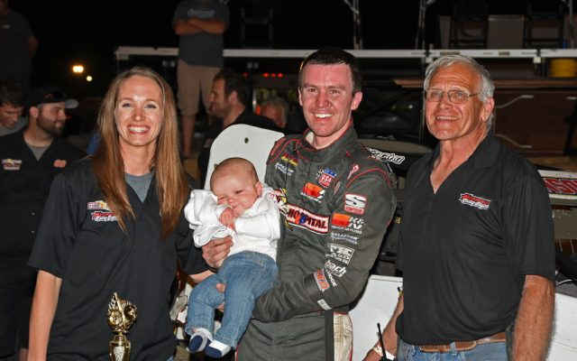 Kody and Jody Swanson hold their 5-month old son in victory lane along with team's ace car chief Bob Hampshire.  [Joe Jennings Photo]