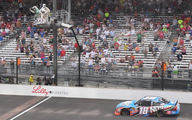 Kyle Busch takes the checkers and victory in the Lilly Diabetes 250.  [Russ Lake Photo]