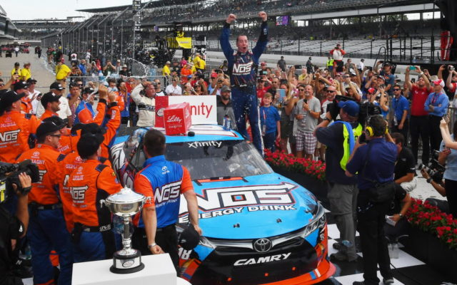 Kyle Busch hops out of the car after winning the Lilly Diabetes 250.  [Russ Lake Photo]