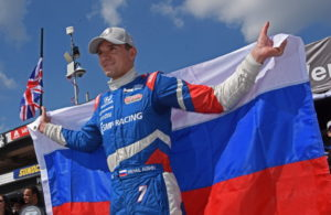 Pole winner Mikhail Aleshin all smiles as he proudly holds Russian flag. [Joe Jennings Photo]