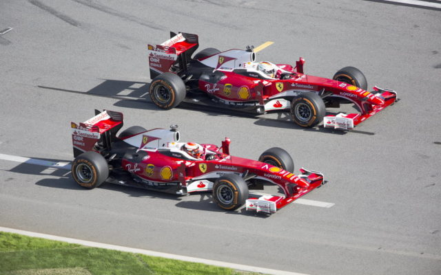 Sebastian Vettel and Kimi Raikkonen driver their F1 Ferraris towards the high banks of the Daytona International Speedway.  [Photo by Thomas Murray]