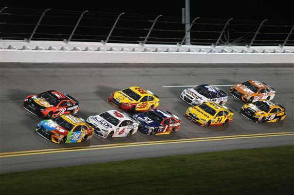 Kyle Busch and Martin Truex Jr. lead a pack of cars during the Monster Energy NASCAR Cup Series Can-Am Duel 1 at Daytona International Speedway. [Credit: Jerry Markland/Getty Images]
