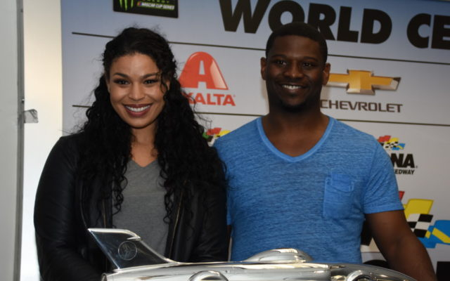 National Anthem vocalist Jordin Sparks, who flew with Thunderbirds, and Honorary starter and NFL Hall of Famer LaDanien Tomlinson pose next to Harley J. Earl winner's trophy.  [Joe Jennings Photo]