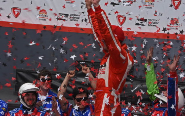 In victory lane, Sebastien Bourdais salutes TV cameras.  [Joe Jennings Photo]