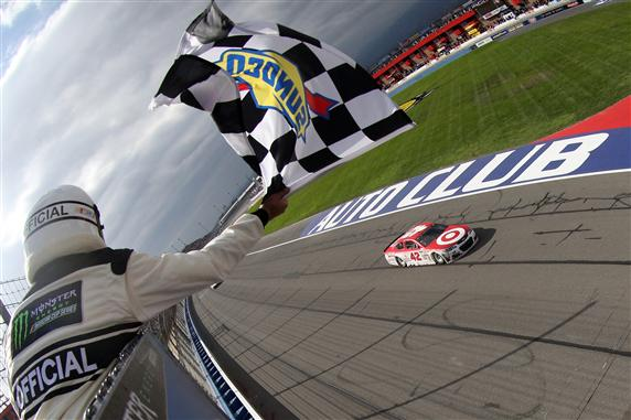 Kyle Larson takes the checkered flag to win the Monster Energy NASCAR Cup Series Auto Club 400 at Auto Club Speedway on March 26, 2017. [Credit: Getty Images]