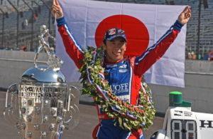 Takuma Sato proudly holds up the Japanese flag. [Joe Jennings Photo]