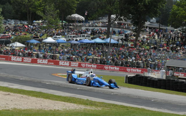 Scott Dixon leads the Kohler Grand Prix in front of a large turn 5 crowd at Road America.  [Dave Jensen Photo]