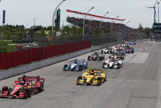 Scott Dixon and Helio Castroneves lead the field to the green flag to start the Honda Indy Toronto. [Photo by: Chris Jones]