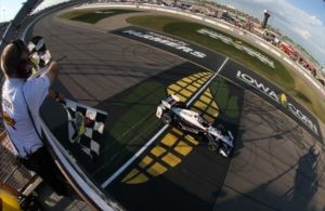 Helio Castroneves takes the twin checkers to win the Iowa Corn 300 at Iowa Speedway.   [Photo by: Chris Jones]