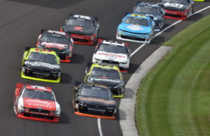 The pack runs through turn one at Indianapolis in the Lilly Diabetes 250. [John Wiedemann Photo]