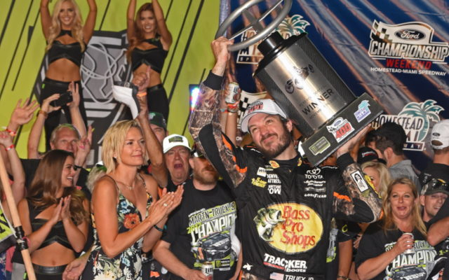 Martin Truex Jr holds up trophy for Winning the race.  [Joe Jennings Photo]