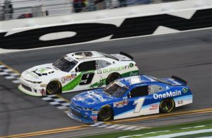 Tyler Reddick, driver of the #9 BurgerFi Chevrolet, crosses the finish line in front of Elliott Sadler to win the NASCAR Xfinity Series PowerShares QQQ 300 at Daytona International Speedway. [Photo by Jared C. Tilton/Getty Images]