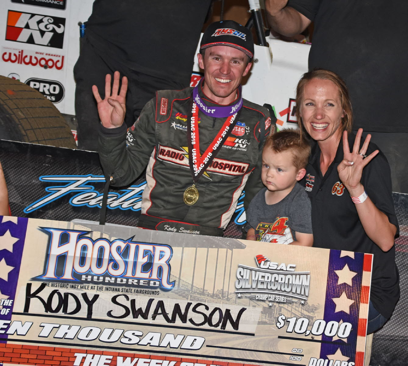 Winner Swanson, wife Jordan and son Trevor hold up four fingers to symbolize his four consecutive victories on the mile dirt track. [Joe Jennings Photo]