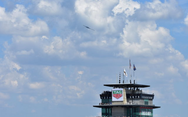 The flyover performed by a B2 Bomber as it slices past the Pagoda at the Indianapolis Motor Speedway.  [John Wiedemann Photo]