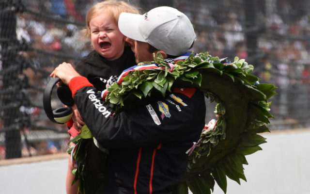 Will Power holds his daughter, who sheds tears instead of joy.  [Joe Jennings Photo]