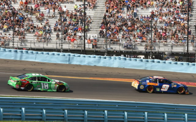 Midway through race, Chase Elliott passes Kyle Busch in turn 1.  [Joe Jennings Photo]