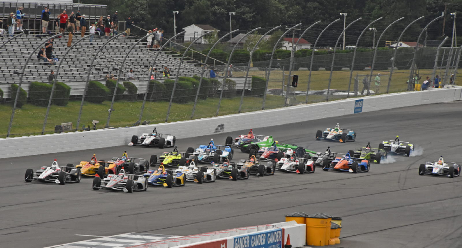 As the field races to the starting line, bedlam occurs in the back with Graham Rahal up against the outer wall and Spencer Pigot (green car) spins into the inner wall. [Joe Jennings Photo]