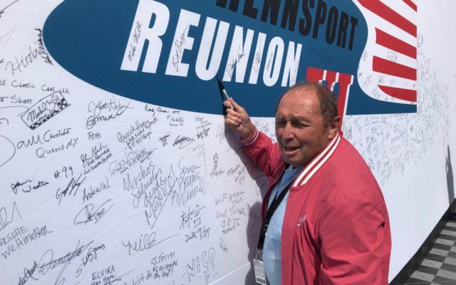 Jochen Mass signing the Rennsport banner.  [Photo by Jack Webster]