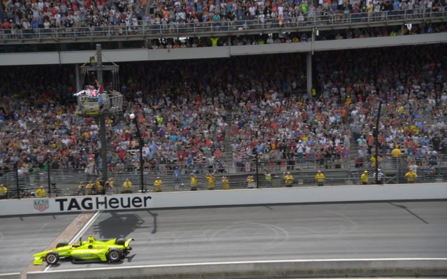 Simon Pagenaud crosses the yard of bricks with the checkered flags in the air, winning the Indianapolis 500.  [Russ Lake Photo]