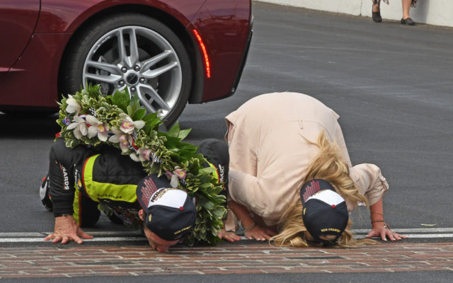 Simon Pagenaud and fiancé Hailey McDermott kiss Yard of Bricks.  [Joe Jennings Photo]