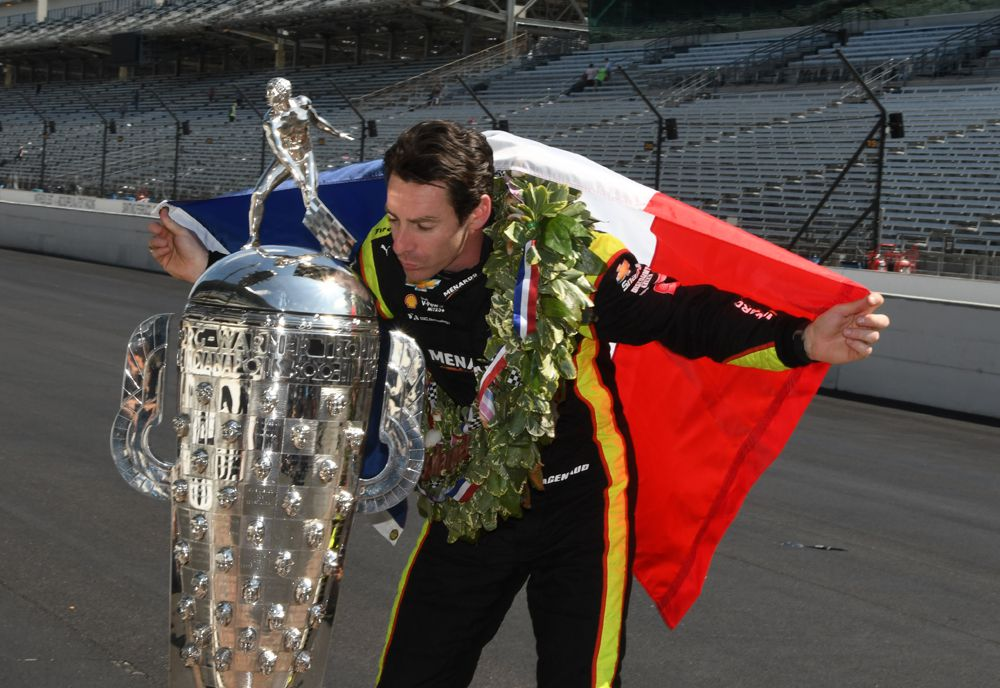 Wrapped in the French flag poses beside Borg-Warner trophy. [Joe Jennings Photo]
