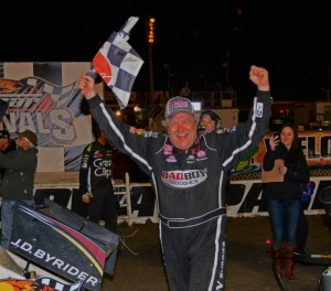 Winner Steve Kinser all smiles as he waves checkered flag to delight of the crowd.  [Joe Jennings Photo]