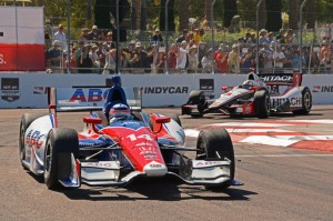 In turn 10, Takuma Sato races ahead of Helio Castroneves with large crowd shown in background.  [Joe Jennings Photo]