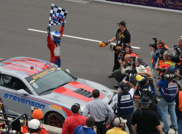 Robin Liddell waves the checkers and celebrates the Brickyard Grand Prix victory.  [Russ Lake Photo]