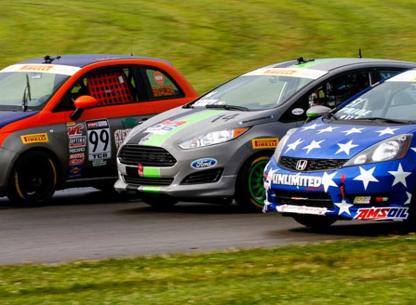 Nathan Stacy (14) battles for position between Austin Snader (99) and Brian Price (51) in TCB Class action. [Andy Clary Photo]