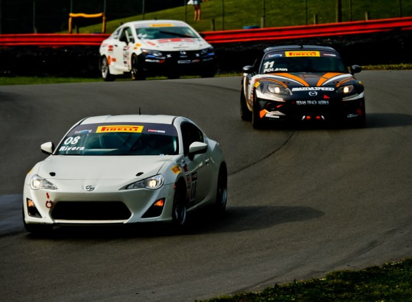 Tony Rivera is chased by Adam Poland in TC class racing action. [Andy Clary Photo]