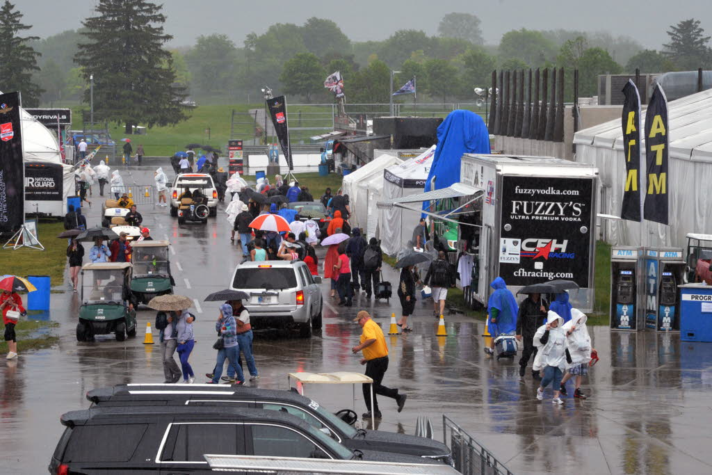 People scurry as rain hits the Indianapolis Motor Speedway, washing out Saturday's scheduled qualifying. [Russ Lake Photo]