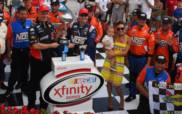 Kyle Busch celebrates the win with his family in victory lane at the Indianapolis Motor Speedway.  [Russ Lake Photo]