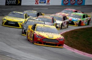Joey Logano leads a pack of cars at Martinsville Speedway. [Credit: Todd Warshaw/NASCAR via Getty Images]