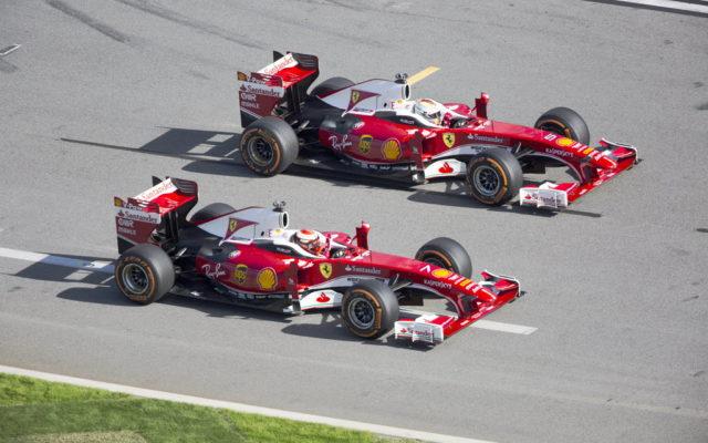 Sebastian Vettel and Kimi Raikkonen driver their F1 Ferraris towards the high banks of the Daytona International Speedway.  [Photo by Thomas Murray]