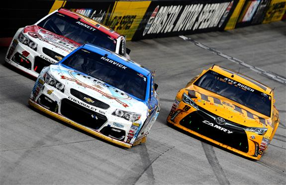 Kevin Harvick leads a pack of cars during the Bass Pro Shops NRA Night Race at Bristol Motor Speedway. [Photo by Brian Lawdermilk/Getty Images]