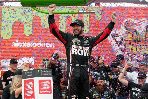 Martin Truex Jr. celebrates in Victory Lane after winning the Monster Energy NASCAR Cup Series Tales of the Turtles 400 at Chicagoland Speedway. [Photo by Brian Lawdermilk/Getty Images]