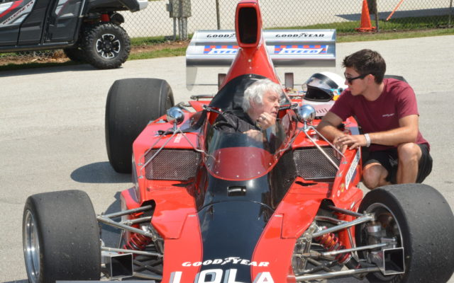 Brian Redman (sitting in car) chatting with crew member outside victory lane in a Lola.  [Dave Jensen Photo]