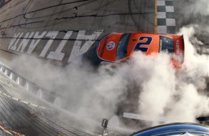 Brad Keselowski celebrates with a burnout after winning the Monster Energy NASCAR Cup Series Folds of Honor QuikTrip 500 at Atlanta Motor Speedway. [Sean Gardner/Getty Images]