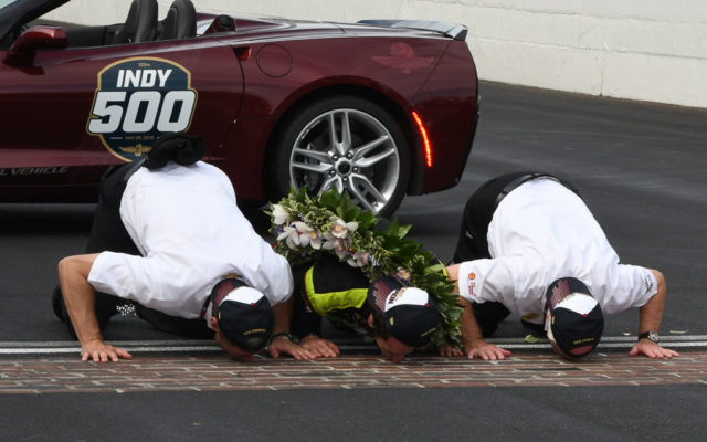 The winning team of Roger Penske (left), Simon Pagenaud (middle) and Tim Cindric (right) kiss the Yard of Bricks.  [Joe Jennings Photo]