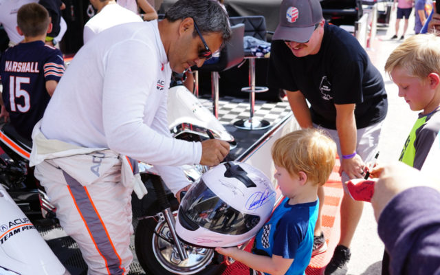 Juan Montoya signing for a small fan.  [Photo by Jack Webster]
