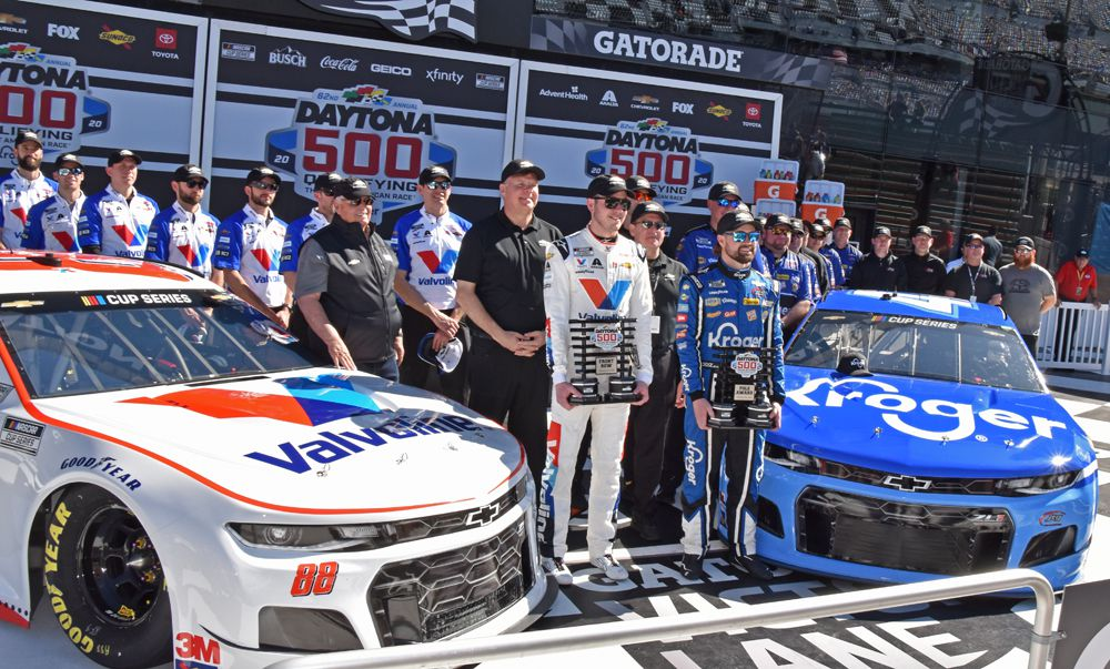 Daytona 500 front-row qualifiers Alex Bowman and Ricky Stenhouse Jr. pose with their crews and Chevrolets. [Joe Jennings Photo]