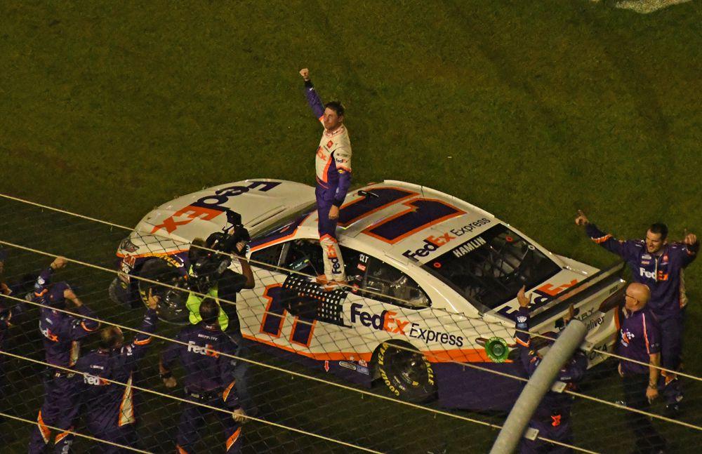 Winner Denny Hamlin salutes the crowd with team members in foreground. [Joe Jennings Photo]
